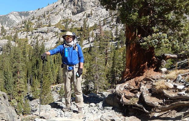 Ben Spillman standing by the Sierra Juniper at John Muir Corner