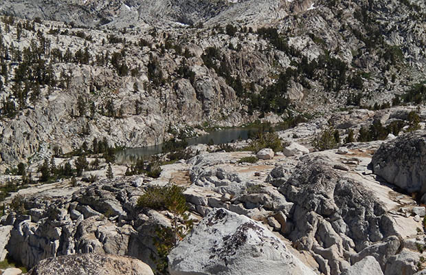 Izaak Walton Lake surrounded by steep granite slabs and cliffs.