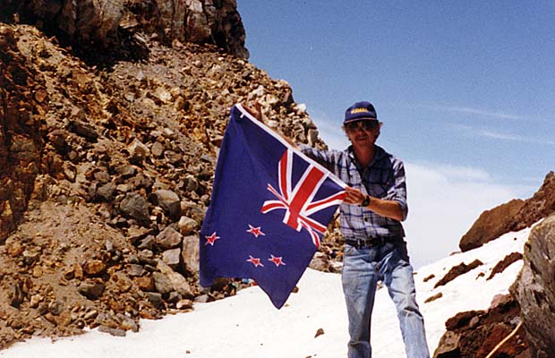 Graham on the summit of Mount Egmont in 1991, proudly holding the New Zealand flag.
