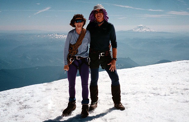 Lucy and Peter on the summit of Rainier, with the Goat Rocks & Mt Adams behind